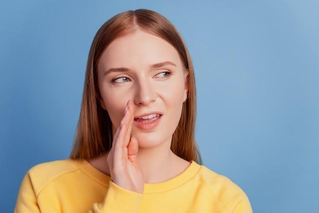 Retrato da boca da palma dama das fofocas astutas e astutas olhar o espaço vazio no fundo azul
