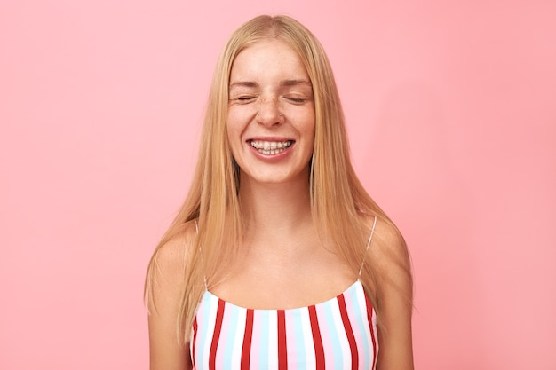 Retrato da cabeça de uma bela jovem com sardas, piercing facial e aparelho, sorrindo animadamente, mantendo os olhos fechados, esperando pela surpresa