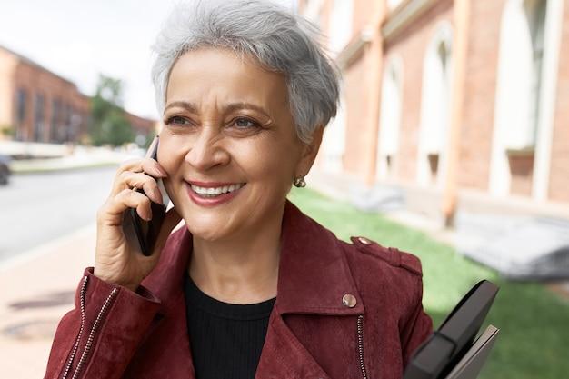 Retrato da cabeça de uma mulher de meia-idade com jaqueta posando na rua da cidade com o celular no ouvido