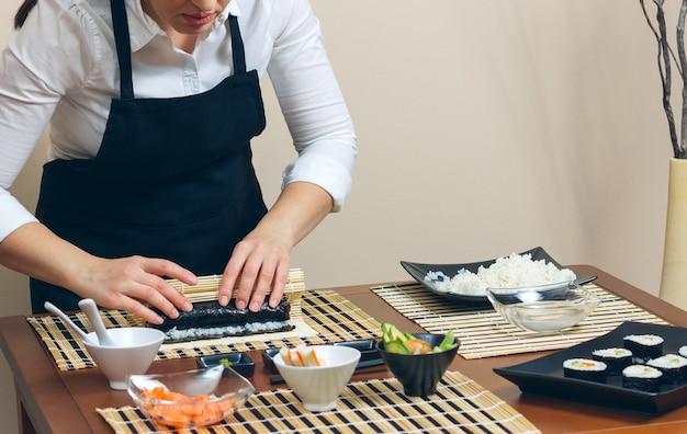 Retrato da chef mulher enrolando um sushi japonês com arroz, abacate e camarão em folha de alga nori