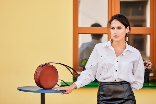 Retrato da cidade da senhora elegante na saia de couro e camisa branca com bolsa de mão de couro
