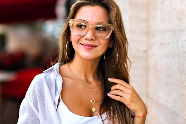 Retrato da cidade de estilo de vida de incrível atraente jovem morena usando óculos claros da moda bege e joias de ouro, cores suaves e quentes, estilo minimalista.
