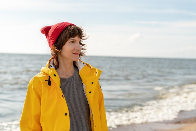 Retrato da cintura de uma mulher madura com capa amarela brilhante e chapéu vermelho na costa