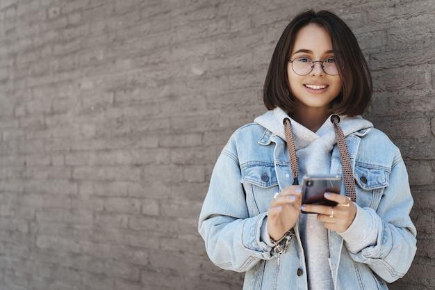 Retrato da cintura para cima de alegre jovem aluna, garota usando telefone celular na rua, mensagens, esperando por um amigo do lado de fora, usando o aplicativo de mapa ou enviando mensagens de texto para alguém, sorrindo a câmera perto da parede de tijolos.