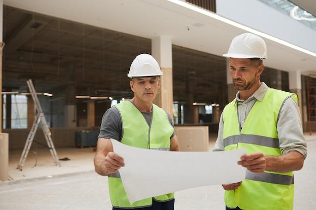 Retrato da cintura para cima de dois empreiteiros de construção profissionais olhando plantas enquanto estão no canteiro de obras,