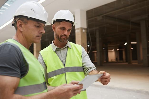 Retrato da cintura para cima de dois empreiteiros de construção profissionais usando tablet digital enquanto estão no canteiro