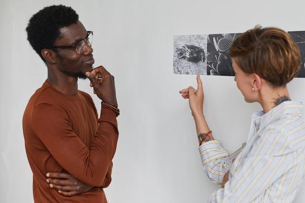 Retrato da cintura para cima de dois jovens discutindo arte enquanto exploram a exposição da galeria moderna,