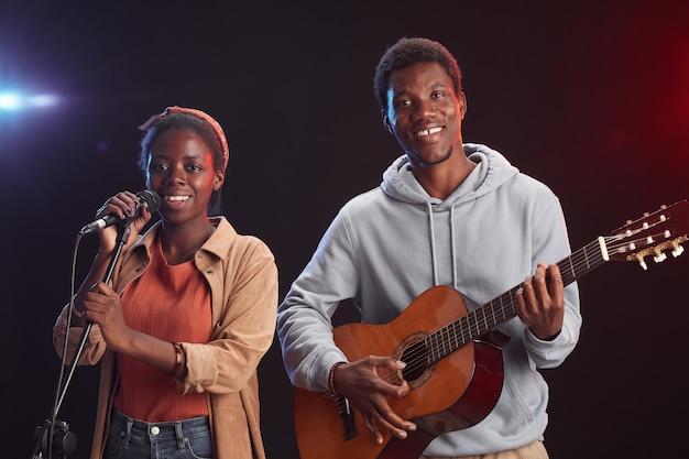 Retrato da cintura para cima de dois músicos afro-americanos tocando violão no palco e cantando ao microfone sorrindo