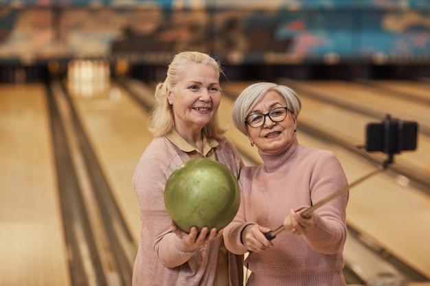 Retrato da cintura para cima de duas mulheres idosas tirando fotos de selfie enquanto jogava boliche e se divertia na pista de boliche, copie o espaço