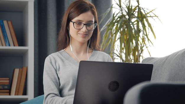 Retrato da cintura para cima de jovem morena positiva sentada no sofá com laptop e fones de ouvido em casa
