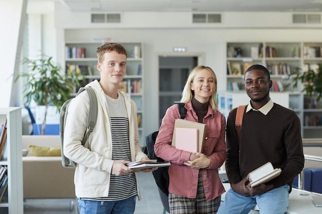 Retrato da cintura para cima de três jovens estudantes sorrindo enquanto estava na biblioteca da faculdade