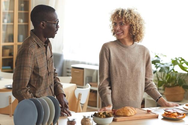 Retrato da cintura para cima de um casal mestiço moderno conversando alegremente enquanto cozinha para um jantar dentro de casa,