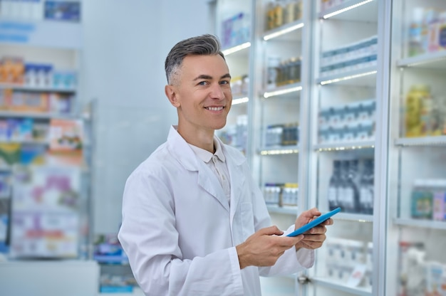 Retrato da cintura para cima de um farmacêutico bonito e alegre ao lado de prateleiras com diferentes produtos de saúde