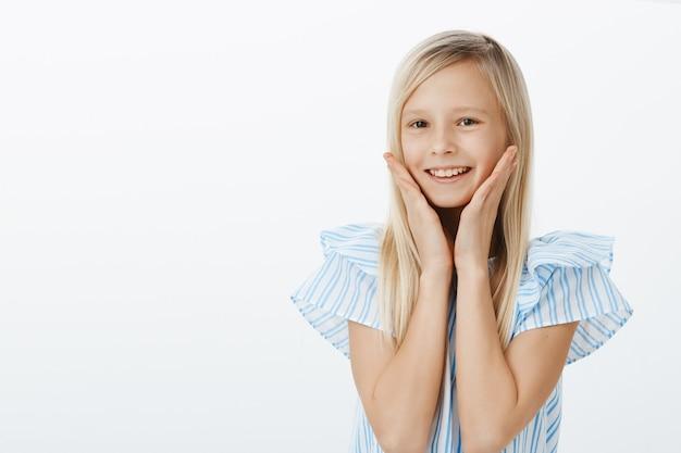 Retrato da cintura para cima de uma adorável criança positiva e satisfeita com cabelos loiros, sorrindo amplamente com o elogio recebido e segurando as mãos nas bochechas, sentindo-se ótima e fofa