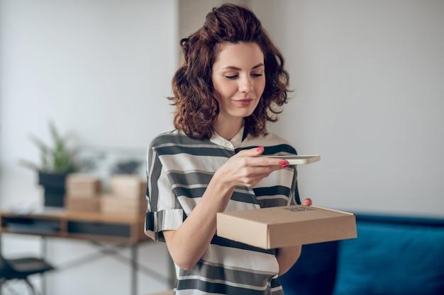 Retrato da cintura para cima de uma bela jovem caucasiana segurando seu celular sobre uma caixa de papelão