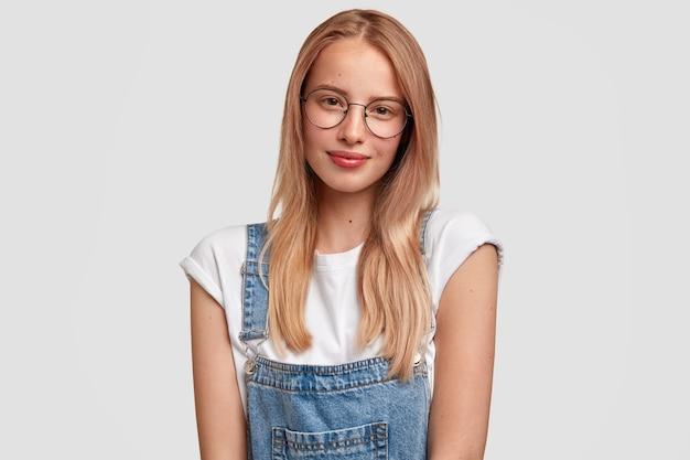 Retrato da cintura para cima de uma bela jovem europeia com cabelo comprido, usa óculos e macacão, sente-se satisfeita ao ouvir os resultados do exame, parece com expressão amigável, isolada sobre uma parede branca