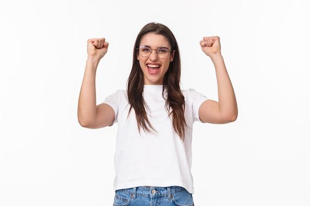 Retrato da cintura para cima de uma garota talentosa e atraente vencendo uma competição, punho levantando as mãos, dança do campeão, dizendo sim, alcance o sucesso