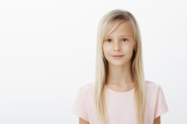 Retrato da cintura para cima de uma linda garota relaxada com cabelo loiro natural em uma camiseta rosa, em pé, confiante e relaxada sobre uma parede cinza, sorrindo ligeiramente, estando de bom humor, esperando na fila