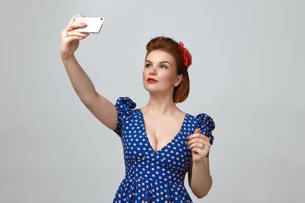 Retrato da cintura para cima de uma linda jovem elegante vestida como uma garota dos anos 1950 segurando um telefone inteligente acima dela e tirando uma selfie