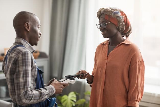 Retrato da cintura para cima de uma mulher afro-americana sorridente pagando serviços de um trabalhador braçal passando o cartão no terminal do banco, copie o espaço