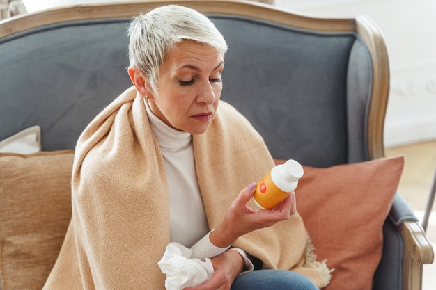 Retrato da cintura para cima de uma mulher idosa olhando para um frasco de comprimidos na mão