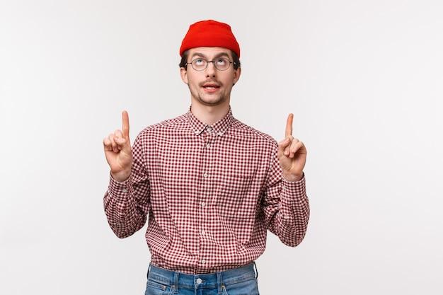 Retrato da cintura para cima engraçado jovem criativo com ratoeira em óculos e gorro vermelho, apontando os dedos para cima e revirando os olhos para cima, como se estivesse vendo algo legal,