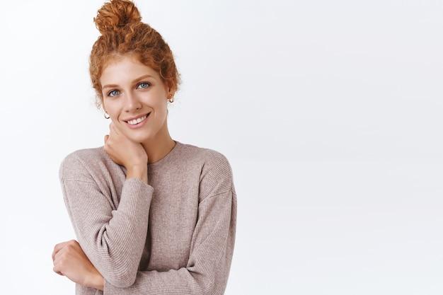 Retrato da cintura para cima, mulher elegante e terna com cabelo ruivo cacheado em um coque bagunçado, cruze um braço, sorrindo modesto e coquete, tocando o pescoço suavemente, parede branca de pé feliz e despreocupada