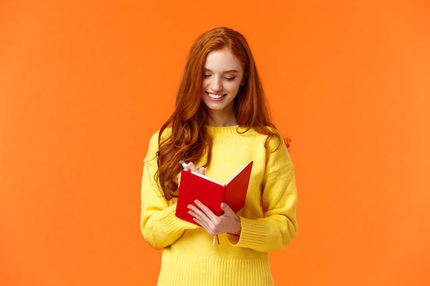 Retrato da cintura para cima mulher ruiva atraente 20 anos escreve em seu diário, lista de tarefas a fazer ou agenda pessoal