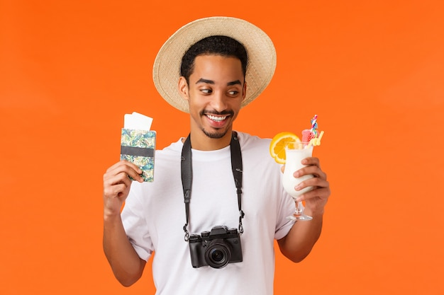 Retrato da cintura para cima satisfeito homem afro-americano em camiseta branca e chapéu, olhando com desejo