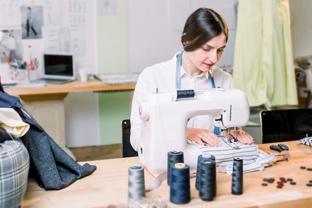 Retrato da costureira da jovem mulher bonita com uma máquina de costura. foto de vista lateral da máquina de costura e costureira no processo de trabalho. negócio de costura. bordado