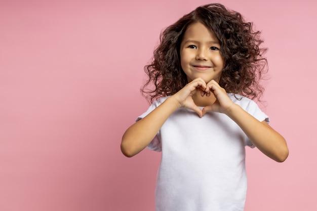 Retrato da doce menina alegre, vestindo camiseta branca, com cabelo escuro encaracolado, mostrando o gesto de coração, olhando de lado sorrindo, isolado de pé.