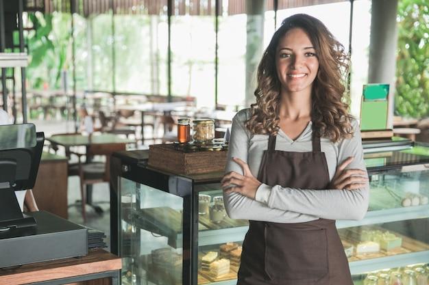 Retrato da dona de um café mestiço sorrindo com orgulho em sua loja