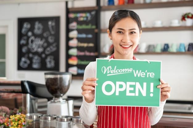 Retrato da dona do café em pé no portão da cafeteria com uma tabuleta aberta