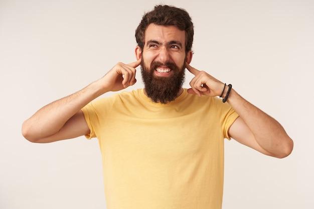 Retrato da emoção de um jovem barbudo irritado ou confuso com os braços segurando as orelhas fechadas olhando para o lado posando