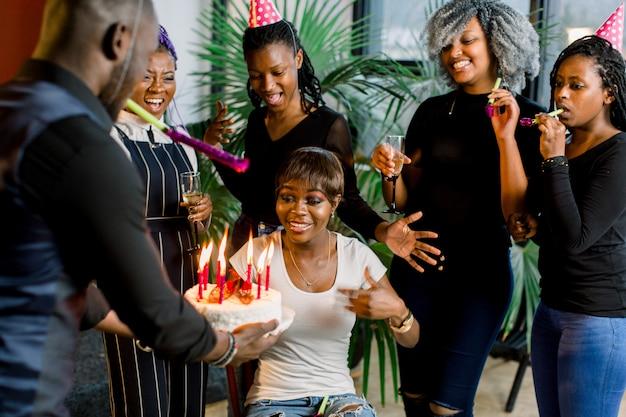 Retrato da encantadora garota afro-americana soprando velas no bolo de aniversário, cercado por amigos na festa