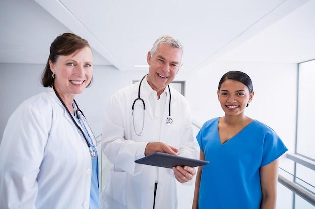 Retrato da enfermeira sorridente e médicos discutindo sobre tablet digital