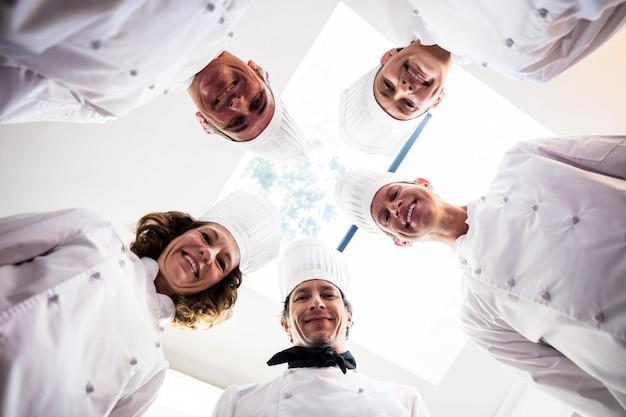 Retrato da equipe de cozinheiros em pé em um círculo vestindo uniformes