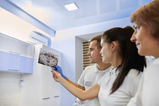 Retrato da equipe de dentista. uma equipe de dentistas revisando radiografias orais no consultório odontológico. odontologia