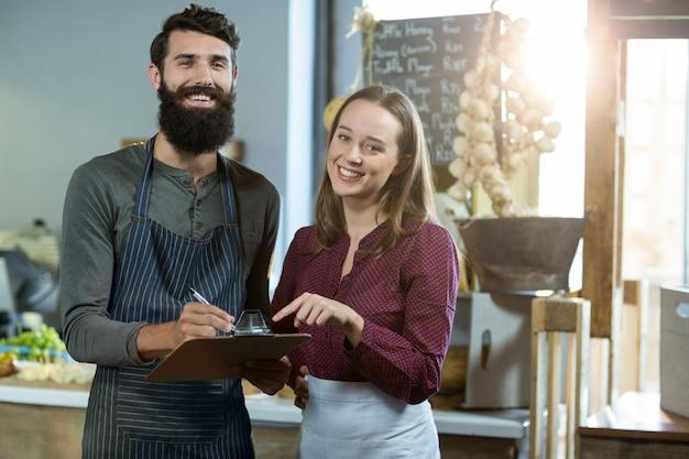 Retrato da equipe de padaria sorridente escrevendo na área de transferência no balcão