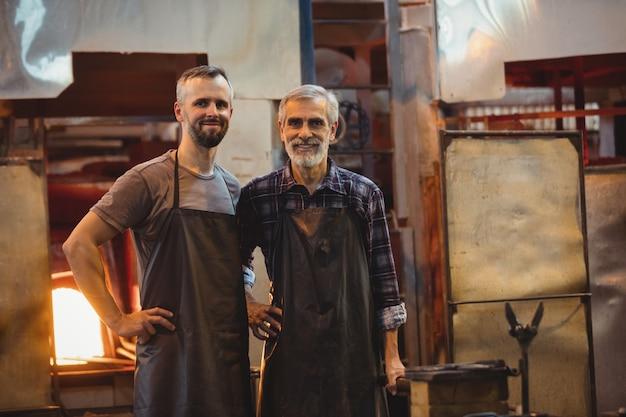 Retrato da equipe de sopradores de vidro com as mãos no quadril