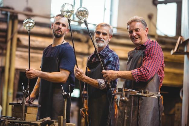 Retrato da equipe de sopradores de vidro, moldando um copo na zarabatana