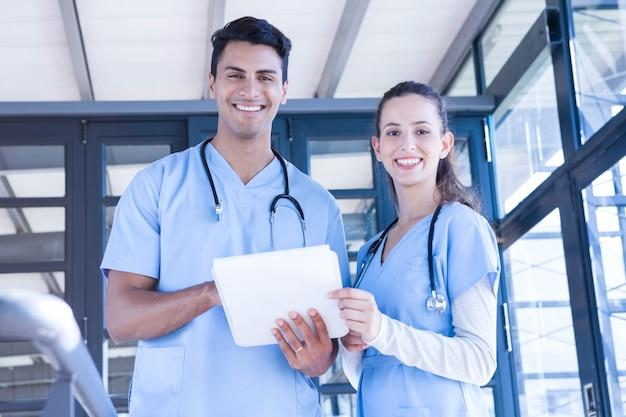 Retrato da equipe médica em pé com o bloco de notas no hospital