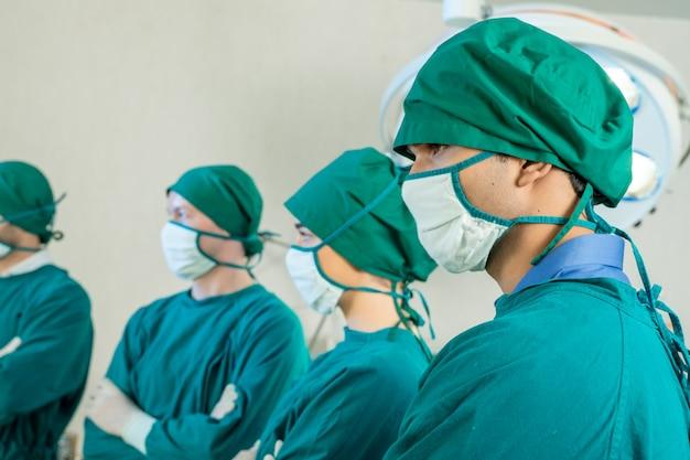 Retrato da equipe profissional médica em pé na sala de operação.