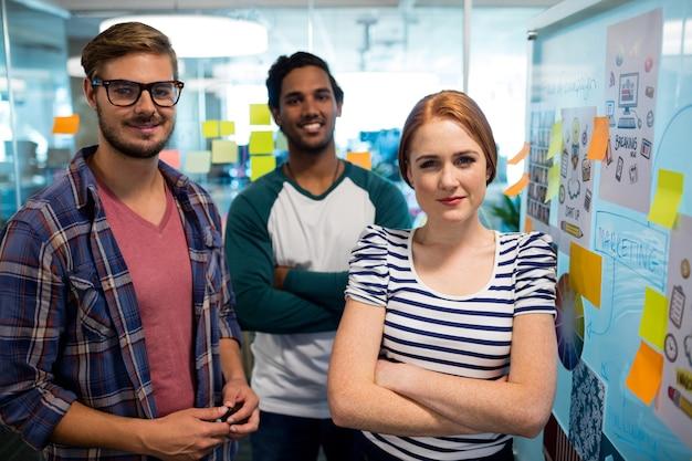 Retrato da equipe sorridente de negócios criativos ao lado de notas adesivas no escritório