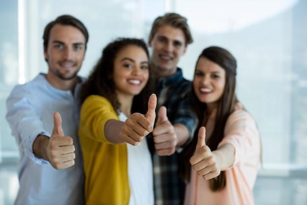 Retrato da equipe sorridente de negócios criativos mostrando os polegares para cima no escritório