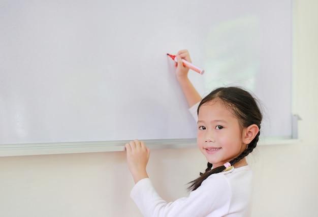 Retrato da estudante feliz que escreve algo no whiteboard com um marcador.