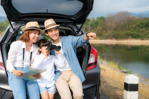 Retrato da família asiática que senta-se no carro com o pai que aponta à vista e à mãe que guardam mapas com a filha que olha a paisagem bonita através dos binóculos durante férias junto no feriado.