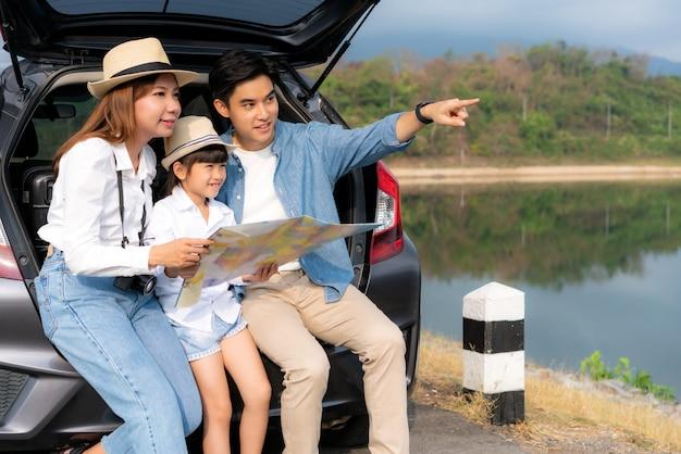Retrato da família asiática que senta-se no carro com o pai que aponta para a vista e a mãe com a filha que olha a paisagem bonita e que guarda mapas enquanto férias junto no feriado. tempo em família feliz.