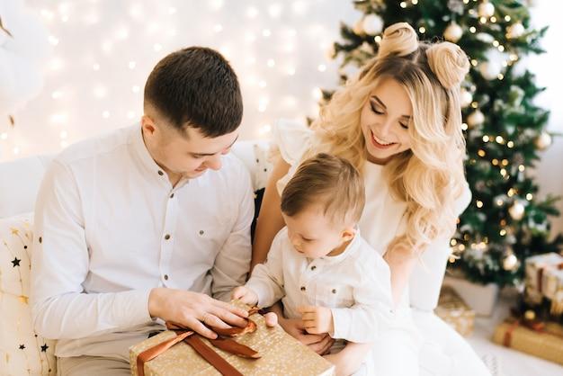 Retrato da família jovem bonita na árvore de natal e fundo branco de algodão. pais atraentes e um filho pequeno abrem presentes de ano novo