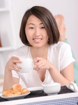 Retrato da fêmea asiática que encontra-se na cama e que come o café da manhã.